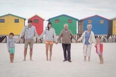 Портрет семьи мульти-поколения держа руки на пляже Стоковые Изображения