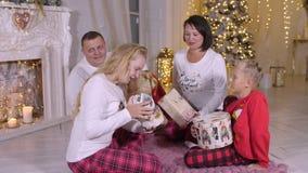 Портрет семьи рождества, счастливые родители дочь и сын смотря подарки в утре рождества акции видеоматериалы