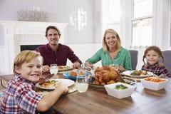 Портрет семьи сидя вокруг таблицы есть еду дома Стоковая Фотография RF
