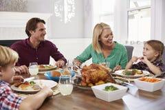 Портрет семьи сидя вокруг таблицы есть еду дома Стоковые Изображения
