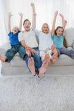 Портрет семьи смотря телевидение и поднимая оружия Стоковая Фотография