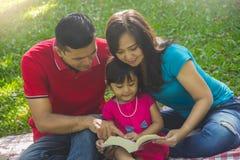 Портрет семьи чтения книги стоковые фотографии rf