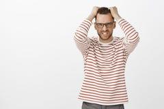 Портрет сердитого надоеданного красивого бородатого мужчины в стеклах, вытягивая волосы из головы и гримасничая от надругательств стоковое изображение rf