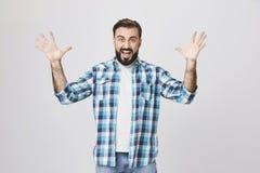 Портрет сердитого умалишённого европейского человека, крича и распространяя его руки пока показывающ жестами, над серой предпосыл стоковая фотография rf