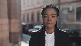 Портрет серьезного Афро-американского положения бизнес-леди на старой улице около бизнес-центра Она смотря акции видеоматериалы