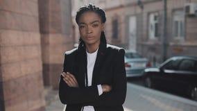 Портрет серьезного Афро-американского положения бизнес-леди на старой улице и пересекая руках Она смотря акции видеоматериалы