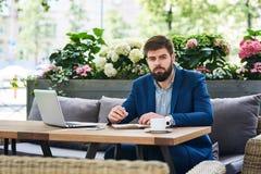Портрет серьезного бизнесмена работая в кафе Стоковые Изображения