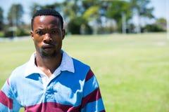 Портрет серьезного игрока рэгби стоя на поле Стоковое фото RF