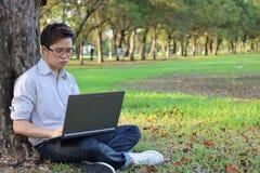 Портрет серьезного молодого бизнесмена работая на его портативном компьютере в парке города с предпосылкой космоса экземпляра Стоковые Фото