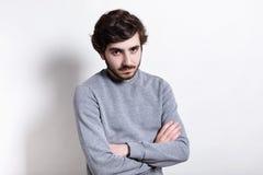 Портрет серьезного молодого бородатого парня при стильный стиль причёсок одетый в вскользь положении свитера пересек руки изолиро Стоковое Фото