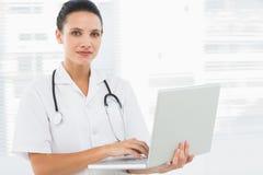 Портрет серьезного молодого женского доктора используя компьтер-книжку Стоковое фото RF
