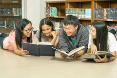 Портрет серьезного молодого студента читая книгу в библиотеке Стоковые Изображения