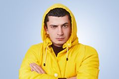 Портрет серьезного парня битника брюнет держит руки пересеченный, носит модный желтый плащ с клобуком, слушает внимательно к внут стоковые фото