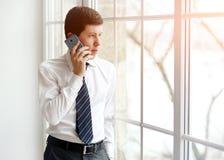 Портрет серьезного работника офиса людей говоря на мобильном телефоне пока стоящ в современном офисе Стоковое Изображение