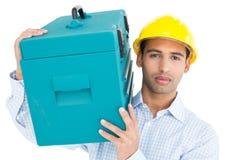 Портрет серьезного разнорабочего в трудной шляпе нося toolbox Стоковое Изображение RF