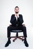 Портрет серьезного сконцентрированного бизнесмена в черном стуле офиса Стоковые Изображения