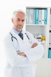 Портрет серьезного уверенно мужского доктора на медицинском офисе Стоковое Фото