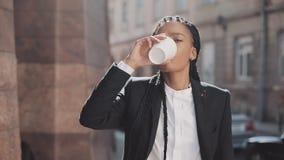 Портрет серьезной Афро-американской бизнес-леди в костюме, идя вокруг города и выпивая кофе Она смотря сток-видео