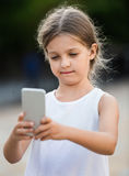 Портрет серьезной девушки смотря мобильный телефон стоковое изображение