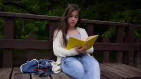 Портрет серьезной книги чтения девочка-подростка и поворачивая склонности страницы сидя на стенде в лесе весной видеоматериал