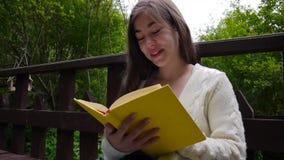 Портрет серьезной книги чтения девочка-подростка и поворачивая склонности страницы сидя на стенде в лесе весной сток-видео