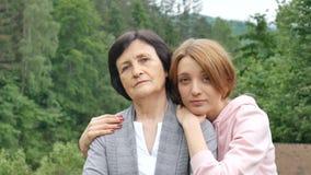 Портрет серьезной матери и взрослой дочери против фона гор летом Счастливая старость сток-видео