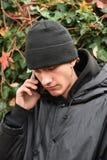 Портрет серьезно молодого человека телефонируя с мобильным телефоном стоковое фото