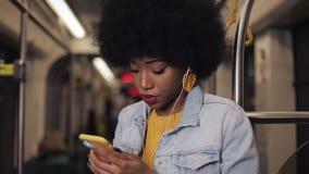 Портрет серьезных Афро-американских женщин в наушниках слушая музыку и просматривая на мобильном телефоне публично видеоматериал