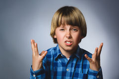 Портрет сердитого мальчика в голубой рубашке при выкрикивать рук вверх изолированный на серой предпосылке студии Отрицательная че Стоковые Изображения RF