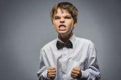 Портрет сердитого мальчика изолированный на серой предпосылке Отрицательная человеческая эмоция, выражение лица closeup Стоковая Фотография