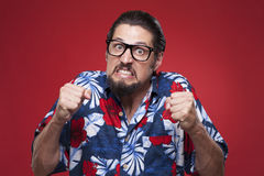 Портрет сердитого молодого человека в гаваиской рубашке с обхваченным fi Стоковые Фото