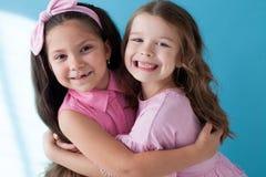 Портрет 2 сестер девушек маленьких девочек на голубой предпосылке стоковое изображение
