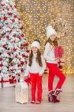 Портрет 2 сестер одной маленькой девочки близко к белой зеленой рождественской елке Девушки в красивых платьях вечера одевают в н Стоковое Изображение