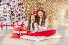 Портрет 2 сестер одной маленькой девочки близко к белой зеленой рождественской елке Девушки в красивых платьях вечера одевают в н Стоковые Фотографии RF