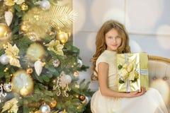 Портрет 2 сестер одной маленькой девочки близко к белой зеленой рождественской елке Девушки в красивых платьях вечера одевают в н Стоковые Фото