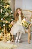 Портрет 2 сестер одной маленькой девочки близко к белой зеленой рождественской елке Девушки в красивых платьях вечера одевают в н Стоковая Фотография