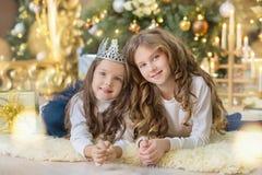 Портрет 2 сестер одной маленькой девочки близко к белой зеленой рождественской елке Девушки в красивых платьях вечера одевают в н Стоковые Изображения