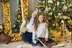 Портрет 2 сестер одной маленькой девочки близко к белой зеленой рождественской елке Девушки в красивых платьях вечера одевают в н Стоковое Фото
