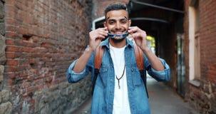 Портрет симпатичного ближневосточного человека принимая усмехаться солнечных очков сток-видео