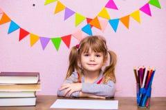 Портрет симпатичной девушки в классе Маленькая школьница сидя на столе и изучать Стоковые Фото