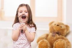 Портрет симпатичной девушки играя с лупой Стоковые Фотографии RF