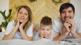 Портрет симпатичной семьи представляя и усмехаясь на кровати в их спальне стоковое фото rf