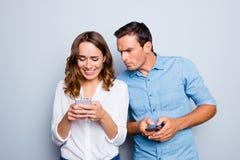 Портрет симпатичных пар с умными телефонами в руках, жизнерадостный c Стоковое Фото