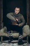 Портрет сильного ратника Викинга точить его шпагу, scandina Стоковые Фото