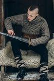 Портрет сильного ратника Викинга точить его шпагу, scandina Стоковая Фотография RF