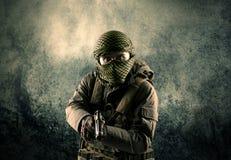 Портрет сильно вооруженного замаскированного солдата с grungy backgroun Стоковые Фото
