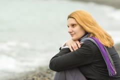 Портрет сидя девушки на пляже на пасмурный холодный день положил его голову в его руки Стоковая Фотография RF