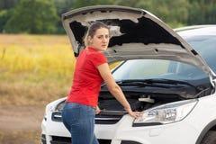 Портрет склонности молодой женщины на сломленном автомобиле в поле Стоковые Фото