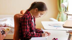 Портрет сконцентрированной девушки делая домашнюю работу в спальне Стоковое фото RF
