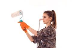 Портрет сконцентрированной детенышами женщины здания брюнет с роликом краски в изолированных руках делает реновацию на белизне Стоковые Фото